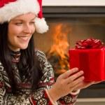 Christmas present woman Santa hat home fireplace — Stock Photo