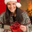 Christmas present woman Santa hat home fireplace — Stock Photo