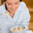 Home breakfast happy woman pajamas eating cereals — Stock Photo