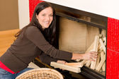 Home fireplace woman put logs happy winter — 图库照片