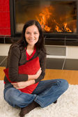 Home fireplace happy woman hold cushion — Stock Photo