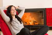 Winter home fireplace woman relax red armchair — Stockfoto