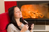 Winter home fireplace woman drink closed eyes — Stock Photo