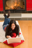 Home living happy woman work computer fireplace — Stock Photo