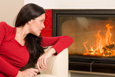 Attractive woman looking into fireplace cozy home — Stock Photo