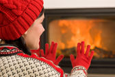 Fireplace warming up happy woman winter home — Stockfoto