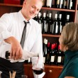 Wine bar waiter serving senior woman glass — Stockfoto