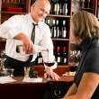 Wine bar waiter serving senior woman glass - Stock Photo