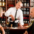 Wine bar senior couple barman pour glass — ストック写真