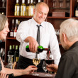 Wine bar senior couple barman pour glass — Stockfoto