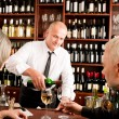 Wine bar senior couple barman pour glass — Stock Photo #8529638