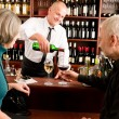Wine bar senior couple barman pour glass - Stock Photo