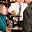 Wine bar senior couple barman pour glass — Stock Photo #8529646