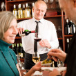 Foto Stock: Wine bar senior couple barman pour glass