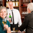 Wine bar senior couple barman discussing — Stock Photo