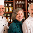 Restaurant manager posing with professional staff - Stock Photo
