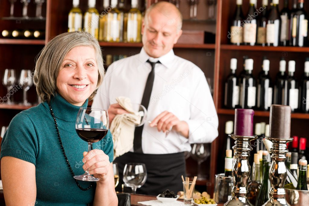 Wine bar senior woman enjoy wine glass in front of bartender — Stock Photo #8529579