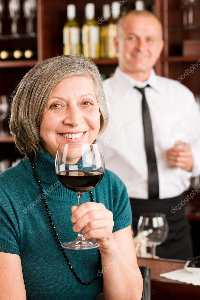 Wine bar senior woman enjoy wine glass in front of bartender  Stock Photo #8529591