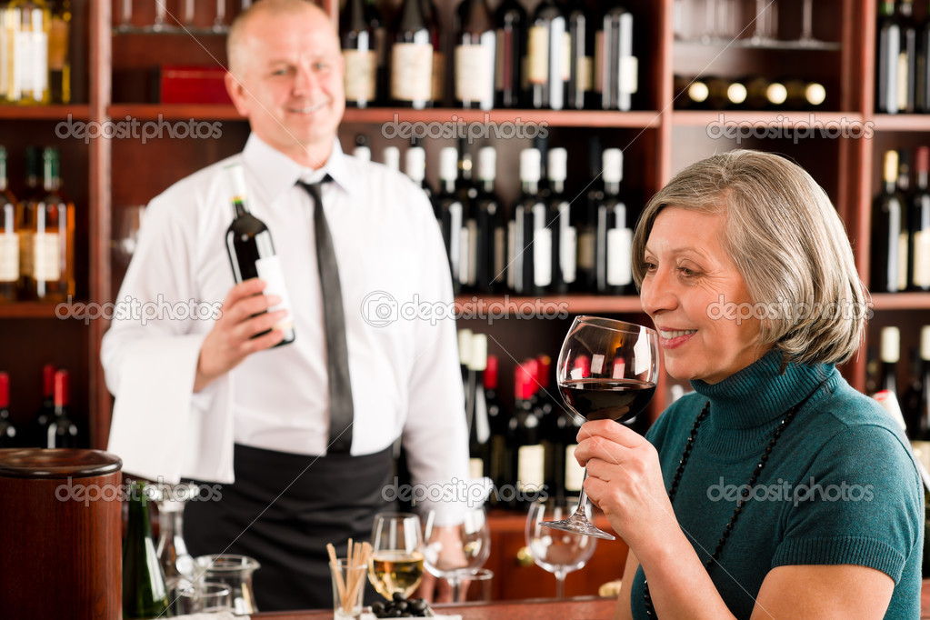Wine bar senior woman enjoy wine glass in front of bartender — Stock Photo #8529596