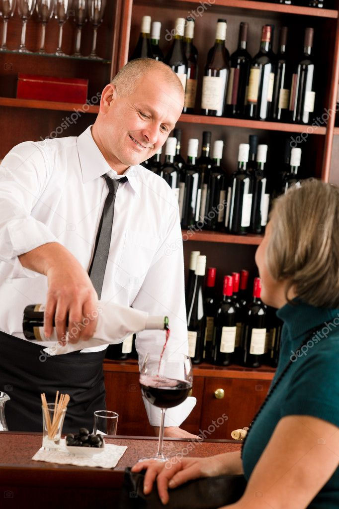 Wine bar professional waiter serve glass senior woman smiling — Stock Photo #8529602
