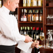 Wine bar waiter opening bottle restaurant - Stock Photo