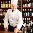 Chef cook smiling serve wine glass restaurant — Stock Photo #8530437