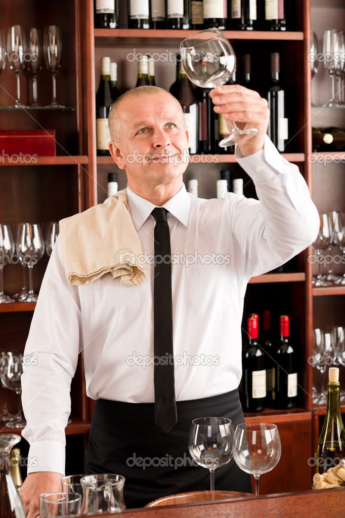Wine bar waiter looking at clean glass in restaurant  Stock Photo #8530221