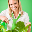 Green business woman water houseplant smiling — Stockfoto