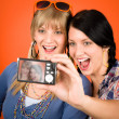 Two young woman friends taking picture smiling - Stock Photo