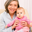 Grandmother hold little baby girl smiling - Stock Photo