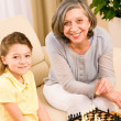 Grandmother and granddaughter play chess together — Stock Photo #8943210