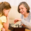 Grandmother and granddaughter play chess together — Stock Photo #8943214