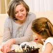 Grandmother and granddaughter play chess together - Stock Photo