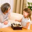 Grandmother and granddaughter play chess together — Stock Photo #8943246