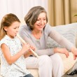 Grandmother teach young girl play flute happy — Stock Photo