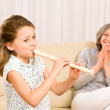 Young girl play flute with proud grandmother — Stock Photo