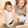 Stock Photo: Grandmother teach young girl learn music notes