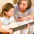 Young girl sing play guitar to grandmother — Stock Photo #8943276