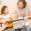 Young girl sing play guitar to grandmother — Foto Stock
