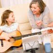 Young girl sing play guitar to grandmother — Stock Photo