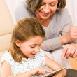 Royalty-Free Stock Photo: Grandmother with granddaughter use touch tablet