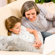 Grandmother with granddaughter use computer — Stock Photo