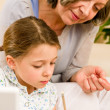 Stock Photo: Grandmother help granddaughter doing homework