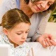 Grandmother help granddaughter doing homework — Stock Photo #8943321