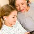 Grandmother and young girl listen music together — Stock Photo