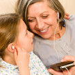 Grandmother and young girl listen music together — Stockfoto
