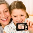 Grandmother and young girl take picture themselves - Stock Photo