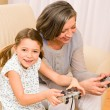 Grandmother and granddaughter play computer game — Stock Photo #8943368