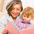 Grandmother and granddaughter read book together — Stock Photo #8943444