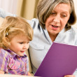 Grandmother and granddaughter read book together — Zdjęcie stockowe #8943459
